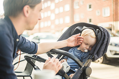 Father looking at baby sleeping on stroller in city - p426m2159438 by Maskot