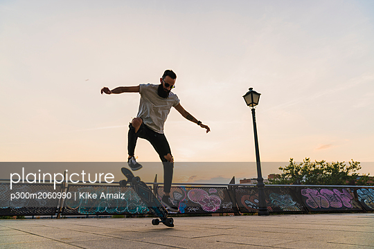Young man doing a skateboard trick in the city at sunset - p300m2060990 von Kike Arnaiz