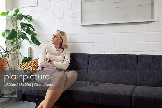 Mature businesswoman sitting on couch in office lounge - p300m2154994 by Gustafsson