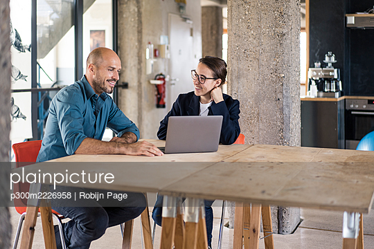 Man and woman using laptop while sitting by table at office - p300m2226958 by Robijn Page