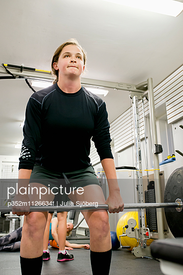 Sweden, Young woman working out with barbell in gym