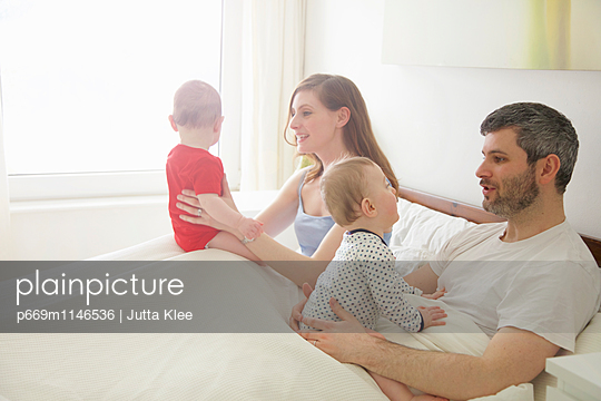 Couple in Bed with Baby Twins - p669m1146536 by Jutta Klee photography
