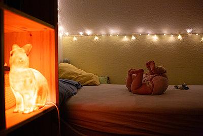 Baby liegt auf einem Bett - p1308m2280029 von felice douglas