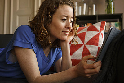 Woman using digital tablet on sofa at home - p301m1579785 by Halfdark