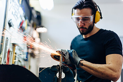 Young man using angle grinder on metal in workshop - p429m2202350 by Sofie Delauw