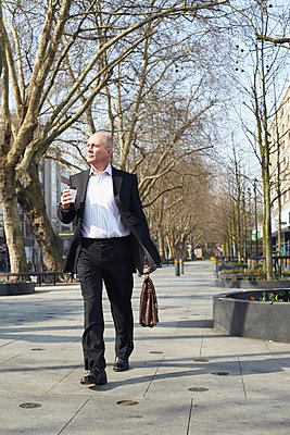 Mature businessman walking on sidewalk with coffee - p429m803576f by Liam Norris