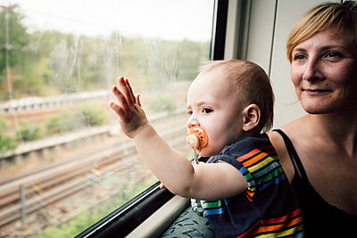 Mother and her baby boy gazing out of train window - p795m2160958 by JanJasperKlein