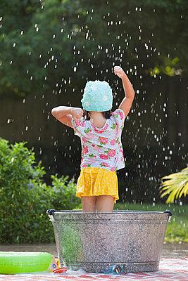Rear view of girl standing in bubble bath in garden splashing soap bubbles - p924m958028f by Kinzie Riehm