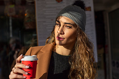Young woman with coffee to go - p975m2222102 by Hayden Verry