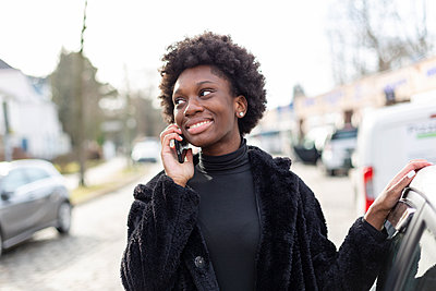 Young dark-skinned woman phoning, portrait - p975m2247763 by Hayden Verry
