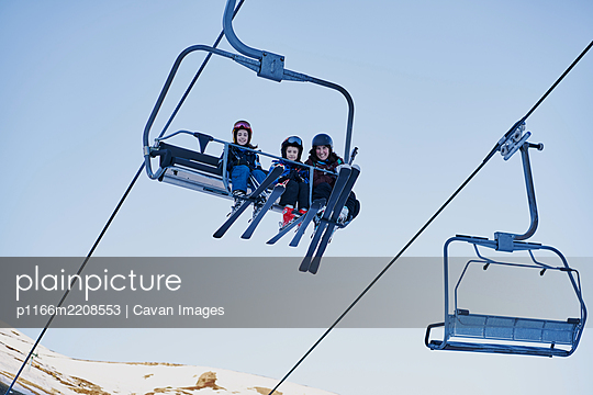 Skiers on a chairlift looking down with a blue background - p1166m2208553 by Cavan Images
