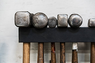 Close up of a selection of hammers hanging on a wall in a metal workshop. - p1100m1544206 by Mint Images