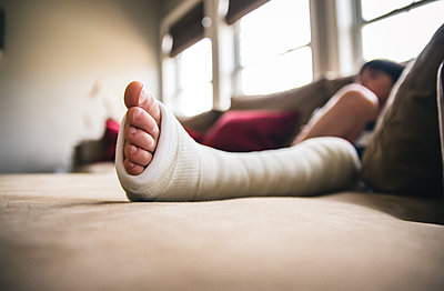 Close-up of boy with fractured leg sitting on sofa at home - p1166m2011863 by Cavan Images