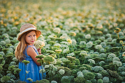 Side view portrait of cute girl wearing hat standing amidst carrot plants on field - p1166m2024861 by Cavan Images