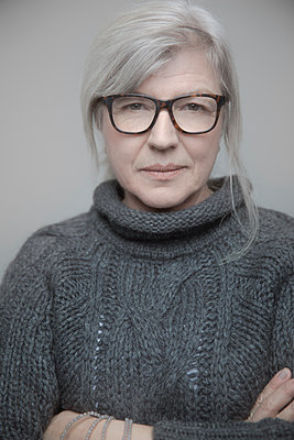 Portrait confident beautiful senior woman with gray hairs and eyeglasses in sweater - p1192m2066279 by Hero Images