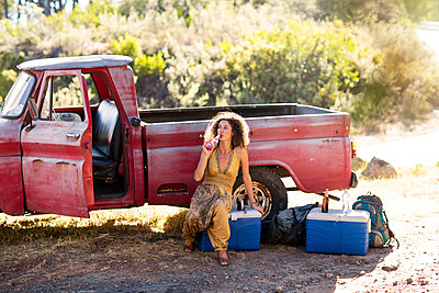 Young woman sitting next to old rusty pick up truck drinking from bottle - p300m1460673 by zerocreatives