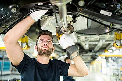 Man working at car underbody in modern factory - p300m2144966 by Fotoagentur WESTEND61