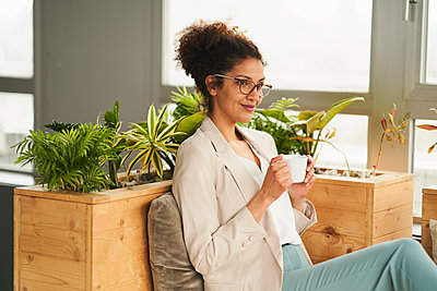 Thoughtful businesswoman with coffee cup by plant at office - p300m2281434 by Annika List