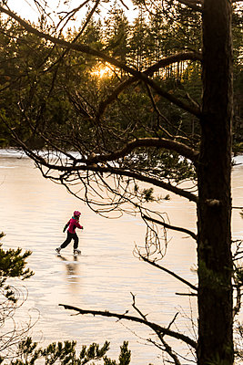 Ice skater on frozen lake - p312m2118580 by Johner