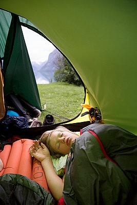 Boy sleeping in tent - p312m996637f by Karin Alfredsson