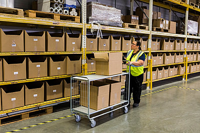 Full length of female worker pushing cart with cardboard boxes by rack at warehouse - p426m2018883 by Maskot