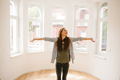Happy young woman in her new apartment - p586m1064870 by Kniel Synnatzschke