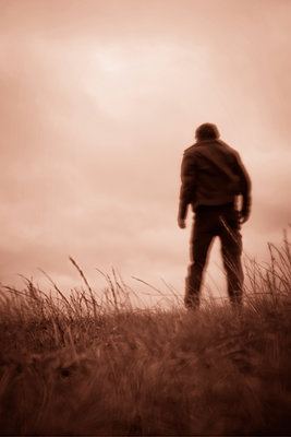 Man walking purposefully through grassy field - p597m2222390 by Tim Robinson