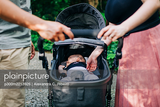 Parents standing by baby sleeping in carriage at park - p300m2213926 by Alexandra C. Ribeiro