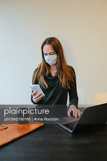 Woman wearing protective mask in office - p312m2190180 by Anna Roström