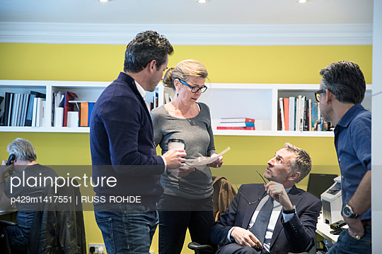 Colleagues in office having discussion - p429m1417551 by RUSS ROHDE
