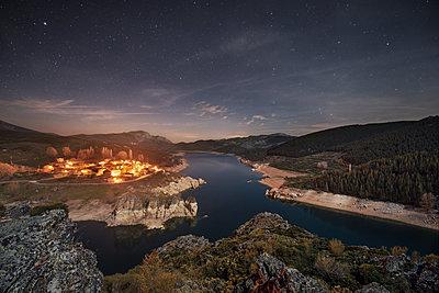 Spain, Castilla y Leon, Palencia, starry night over small village and lake Camporredondo - p300m1460226 by David Herraez Calzada