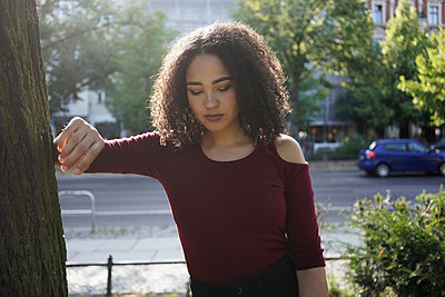 Young woman leaning on tree, Berlin, Germany - p429m2075389 by Tamboly