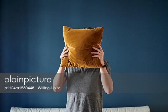Junger Mann versteckt sich hinter einem Kissen - p1124m1589448 von Willing-Holtz