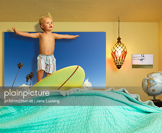 Young Boy Standing On Surfboard, Arms Outstretched, Pretending To Ride Wave Made From Blankets - p1531m2264148 by Jens Lucking