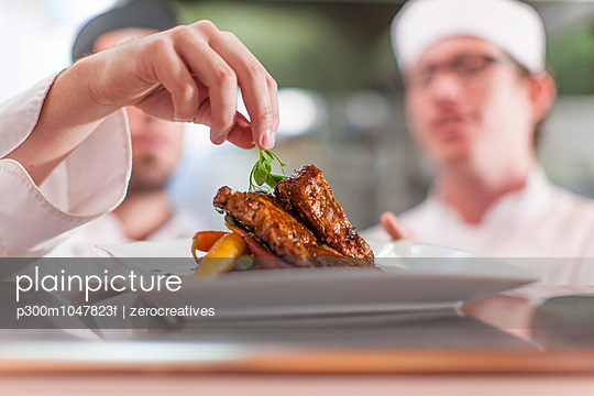 Chef garnishing plate with food - p300m1047823f by zerocreatives