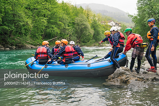 Group of people starting a rafting trip in rubber dinghy on a river - p300m2114245 von Francesco Buttitta