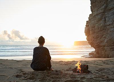 Frau sitzt am Lagerfeuer  - p1124m1112612 von Willing-Holtz