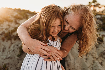Front view of mother hugging young daughter at beach during sunset - p1166m2136566 by Cavan Images