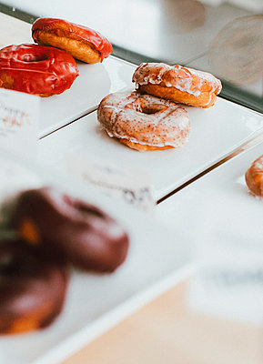 Close up donuts on display in bakery - p301m2213628 by Toby Mitchell