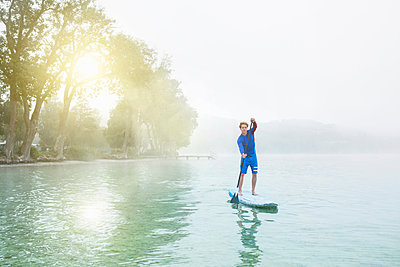Young man stand up paddleboarding on sunlit misty lake Pilsensee, Germany - p429m1156262 by Philipp Nemenz