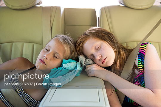 Two Young Girls Asleep in Car After Playing - p1166m2207807 by Cavan Images