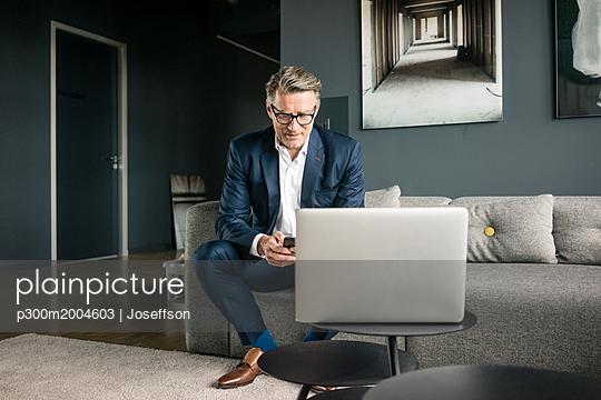Mature businessman using cell phone on couch - p300m2004603 von Joseffson