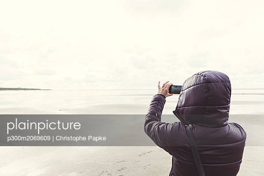 Netherlands, Ouddorp, back view of woman taking selfie on the beach in autumn - p300m2069609 by Christophe Papke