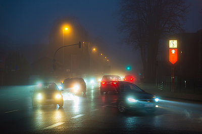 Cars on crossroad in the fog at evening - p300m1204582 by Frank Röder