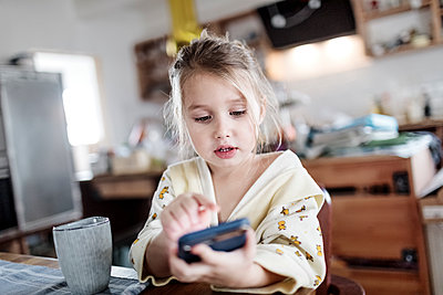 Portrait of little girl sitting at breakfast table in the kitchen using smartphone - p300m2080757 by Katharina Mikhrin