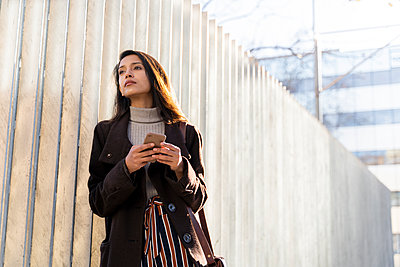 Young woman with smartphone in the city looking around - p300m2166190 by VITTA GALLERY