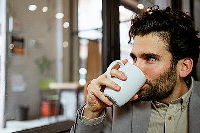 Male freelancer drinking coffee in illuminated cafe - p300m2276350 by Rafa Cortés