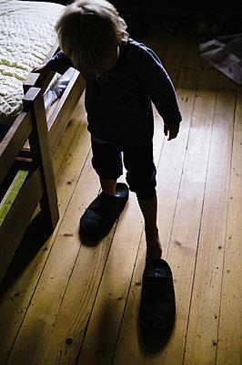 Kleiner Junge in großen Hausschuhen - p819m1066361 von Kniel Mess