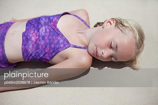 Mädchen döst am Strand - p045m2038678 von Jasmin Sander