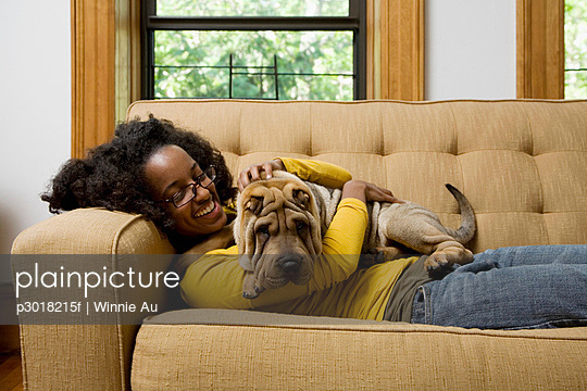 A woman lying a couch with her Shar-Pei - p3018215f by Winnie Au